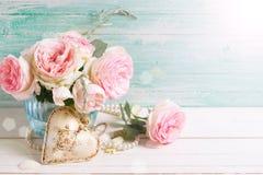 Rosa Rosen blüht im Vase und im dekorativen Herzen Stockfotografie