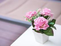 Rosa Rosen des Blumenstraußes in den weißen Vasen-, künstlichen oder gefälschtenblumen Stockbild