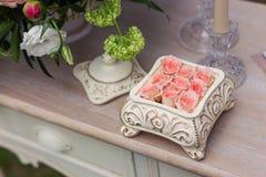 Rosa Rosen in einem keramischen Kasten auf dem table-2 Stockfotografie
