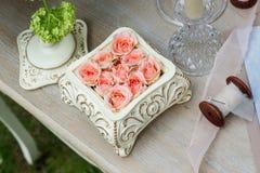 Rosa Rosen in einem keramischen Kasten auf dem table-2 Lizenzfreie Stockbilder