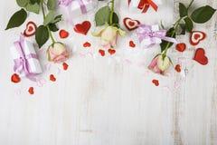 Rosa Rosen, Geschenk und Herzen auf einem hölzernen Hintergrund Lizenzfreie Stockbilder