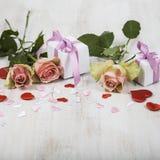 Rosa Rosen, Geschenk und Herzen auf einem hölzernen Hintergrund Stockfoto