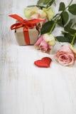 Rosa Rosen, Geschenk und Herzen auf einem hölzernen Hintergrund Lizenzfreies Stockfoto