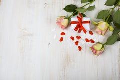 Rosa Rosen, Geschenk und Herzen auf einem hölzernen Hintergrund Lizenzfreie Stockfotografie