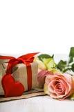 Rosa Rosen, Geschenk und Herzen auf einem hölzernen Hintergrund Stockbild