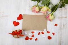 Rosa Rosen, Geschenk und Herzen auf einem hölzernen Hintergrund Stockfotografie