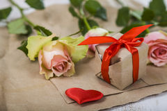 Rosa Rosen, Geschenk und Herzen auf einem hölzernen Hintergrund Stockbilder