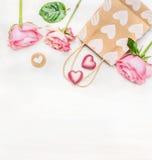 Rosa Rosen mit Einkaufstasche- und Schokoladenherzen auf weißem hölzernem Hintergrund, Draufsicht Rot stieg auf weißen Hintergrun Stockfotografie