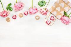 Rosa Rosen mit Schokoladenherzen, Einkaufstasche und rundem Zeichen mit Mitteilung für Sie und mit Liebe auf hellem Hintergrund,  Lizenzfreie Stockbilder