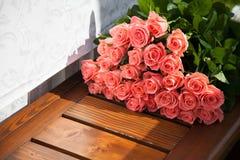 Rosa Rosen sind ein Geschenk Blumenlüge auf einer Holzbank Stockfotos