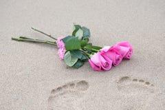 Rosa Rosen und Abdrücke auf nassem Sand Stockbild