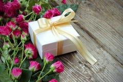 Rosa Rosen und Geschenkbox über Holztisch, Feiertagshintergrund Stockfotografie