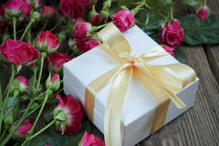 Rosa Rosen und Geschenkbox über Holztisch, Feiertagshintergrund Lizenzfreies Stockbild