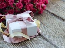 Rosa Rosen und Geschenkbox über Holztisch, Feiertagshintergrund Stockbild