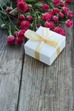 Rosa Rosen und Geschenkbox über Holztisch, Feiertagshintergrund Stockfotos