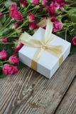 Rosa Rosen und Geschenkbox über Holztisch, Feiertagshintergrund Stockfoto