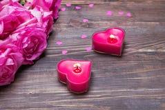 Rosa Rosen und Herz zwei formten Kerzen auf dem hölzernen Hintergrund Stockfotos