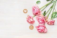 Rosa Rosen und rundes Zeichen mit Mitteilung für Sie und Herz auf weißem hölzernem Hintergrund, Draufsicht Stockbild