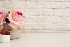 Rosa Rosen verspotten oben Angeredete Fotografie Backsteinmauer-Produkt-Anzeige Erdbeeren auf weißem Schreibtisch Vase mit rosafa Stockfotos