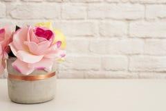 Rosa Rosen verspotten oben Angeredete Fotografie Backsteinmauer-Produkt-Anzeige Weißer Schreibtisch Vase mit rosafarbenen Rosen M Stockfotos