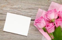 Rosa Rosenblumenstrauß und leere Grußkarte über Holztisch Lizenzfreies Stockbild