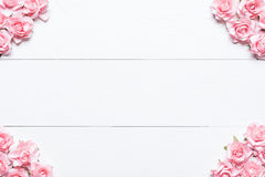 Rosa Rosenrahmen auf weißem Holztisch mit leerem copyspace Stockfotografie