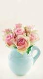 Rosa rosor i en blå vas arkivfoton
