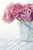 Rosa rosor i en vit snör åt vasen Arkivfoto