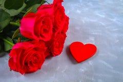 Rosa rosor med röda stearinljus i formen av en hjärta på en grå bakgrund Mall för mars 8, mors dag, valentin dag Royaltyfri Fotografi