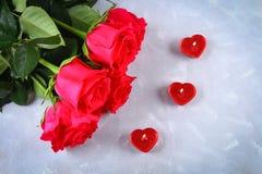 Rosa rosor med röda stearinljus i formen av en hjärta på en grå bakgrund Mall för mars 8, mors dag, valentin dag Royaltyfri Foto