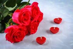 Rosa rosor med röda stearinljus i formen av en hjärta på en grå bakgrund Mall för mars 8, mors dag, valentin dag Arkivfoto