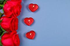 Rosa rosor med röda stearinljus i formen av en hjärta på en grå bakgrund Mall för mars 8, mors dag, valentin dag Royaltyfri Bild