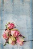 Rosa rosor på den texturerade tabellen Fotografering för Bildbyråer
