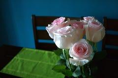 Rosa rosor på en äta middag tabell Royaltyfri Foto