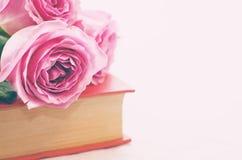 Rosa rosor på en bok Royaltyfri Fotografi