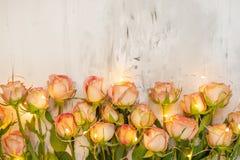 Rosa rosor på en marmorbakgrund med den atmosfäriska girlanden, en begreppsgåva för din favorit- feriebakgrund, årsdag, arkivbilder