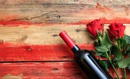 Rosa rossa Bottiglia e rose rosse del vino rosso su fondo di legno immagini stock libere da diritti