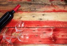 Rosa rossa Bottiglia e vetri del vino rosso su fondo di legno Immagine Stock