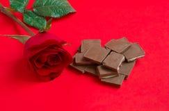Rosa rossa con cioccolato su fondo rosso Immagine Stock