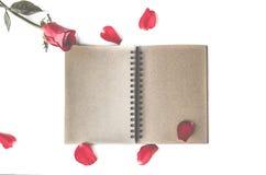 rosa rossa con i petali ed il taccuino marrone per il fondo del biglietto di S. Valentino isolato su fondo bianco fotografia stock libera da diritti