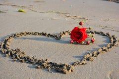 Rosa rossa e cuore sulla spiaggia Immagine Stock