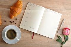 Rosa rossa e una tazza di caffè con un croissant e un diario con il giorno Fotografia Stock