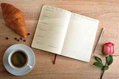 Rosa rossa e una tazza di caffè con un croissant e un diario con il giorno Immagini Stock Libere da Diritti