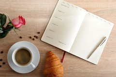Rosa rossa e una tazza di caffè con un croissant e un diario con il giorno Fotografie Stock Libere da Diritti