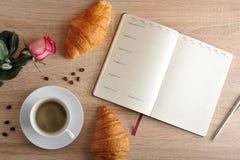 Rosa rossa e una tazza di caffè con un croissant e un diario con il giorno Fotografie Stock