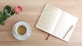 Rosa rossa e una tazza di caffè e un diario con i giorni della settimana Fotografie Stock Libere da Diritti