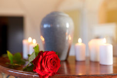 Rosa rossa ed urna di cremazione con le candele brucianti Fotografia Stock