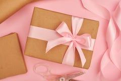 Rosa satängband och för sax gåvaask nära på rosa flatlay Royaltyfria Bilder