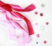 Rosa satängband och knappar Fotografering för Bildbyråer