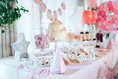 Rosa Schokoriegel für ersten Geburtstag Süße Tabelle und großer Kuchen für ersten Geburtstag stockbild